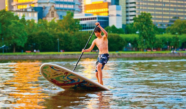 Ein SUP-Paddler des Frankfurter Kanu-Vereins vor der Frankfurter Skyline