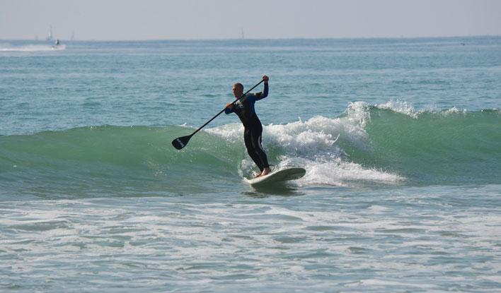 Ein SUP Paddler surft auf einer Welle