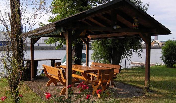 überdachte Laube mit Tisch und Bänken am FKV Außengelände